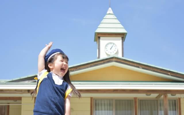 幼稚園の前で手を上げる少女